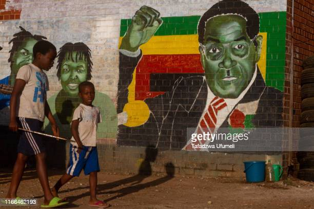 Children pass infront of a wall with a mural of the Robert Mugabe, a day after his death on September 7, 2019 in Harare, Zimbabwe. Mugabe died on...