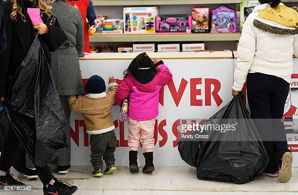 Children peek over the counter to get a view of all the toys at the 86th annual Denver Santa Claus Shop at the old Kmart store near Evans Ave and...
