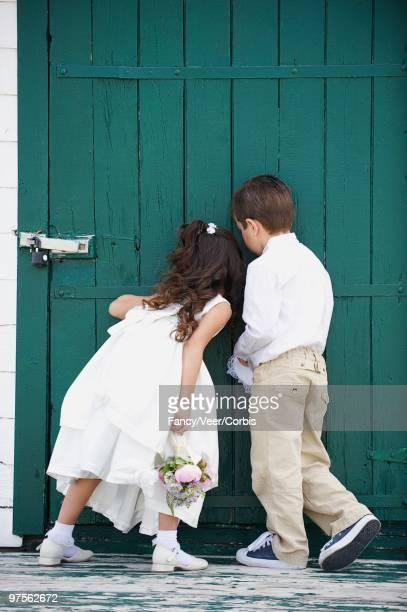 children peeking in door - pageboy stock pictures, royalty-free photos & images