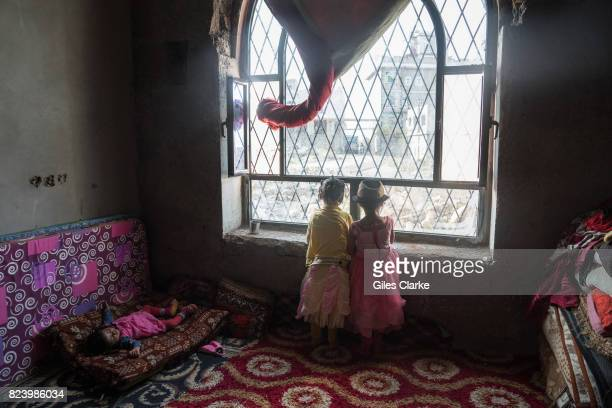 Children peer out of a window in a former government building in the suburbs of Ibb The building was provided by local authorities to house 53...