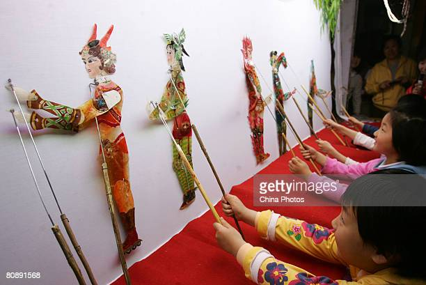 Children perform a shadow play themed 'Five Fuwas Usher The Olympics' under the direction of folk artists to mark the upcoming 100daycountdown to the...