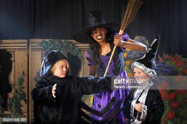 children (4-9) performing on stage, portrait of girl in witches costume - school play stock photos and pictures