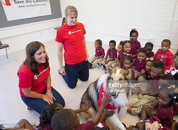 Children pet Save the Children's animal ambassador Lassie as Erin Bradshaw and Sarah Thompson prepare to read a book at a special Katrinaanniversary...