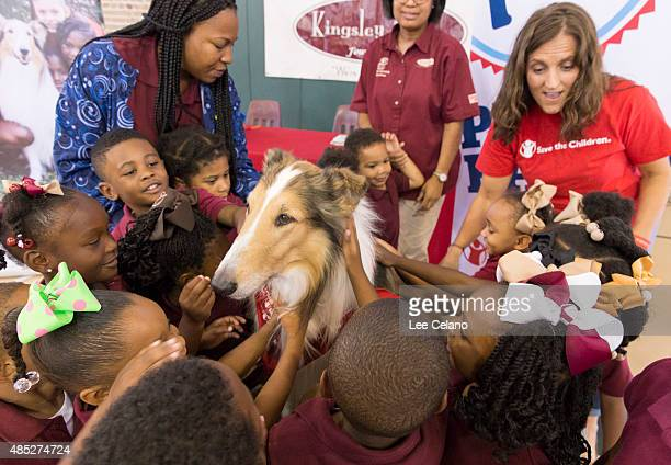 Children pet Save the Children's animal ambassador Lassie as Erin Bradshaw Save the Children Sr Director for Emergency Preparedness looks on at a...