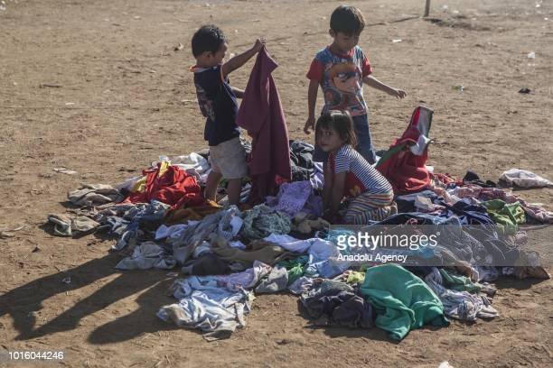 Children pick clothes which are donated for people affected by earthquake at a temporary shelter in Lombok Indonesia on August 13 2018 According data...