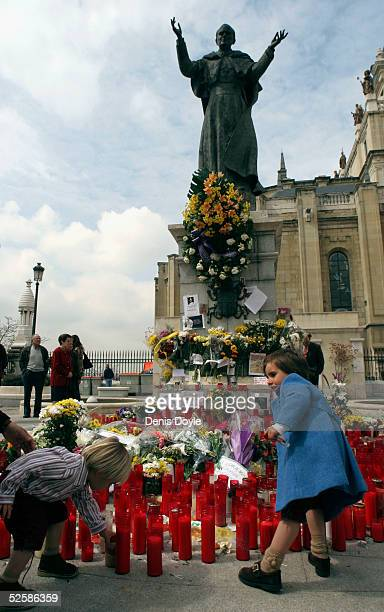 Children place candles under a statue of Pope John Paul II at the Almudena Cathedral on April 4 2005 in Madrid Spain The Vatican announced today that...