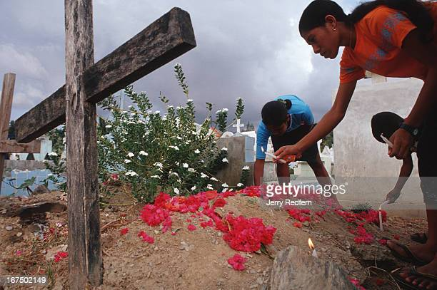 Children place flowers and candles on the grave of their father Jose de Carvalho in the Santa Cruz cemetery The cemetery was the site of a massacre...