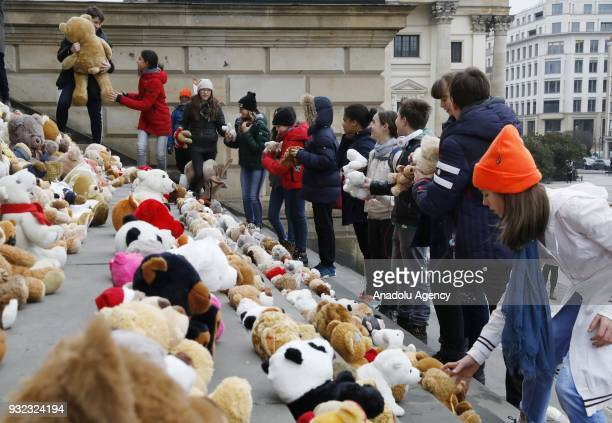 Children place Teddy bears on the stairs of the Concert Hall during 'Teddy Bear action Beyond Survival' organized by World Vision in Berlin Germany...