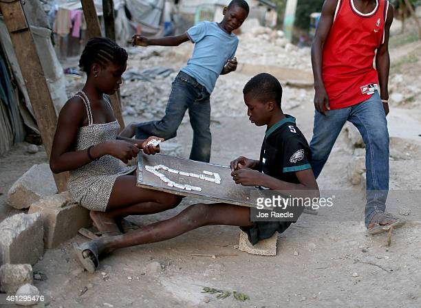 Children play a game of dominoes as they hang out together near the homes made out of tin and tarps that their families built over the land where...