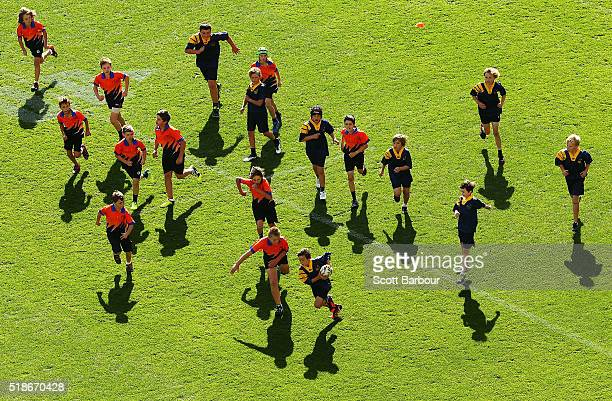 Children play a game of touch football during the half time break of the round five NRL match between the Melbourne Storm and the Newcastle Knights...