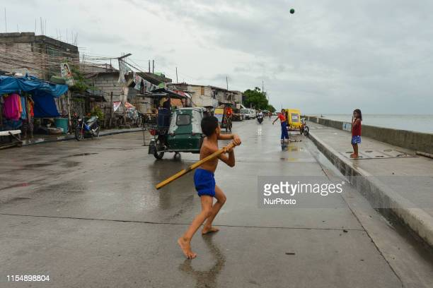 Children play a street baseball near the Pasig River in Baseco Compound in Manila The Batangas Shipping and Engineering Company Compound is the...