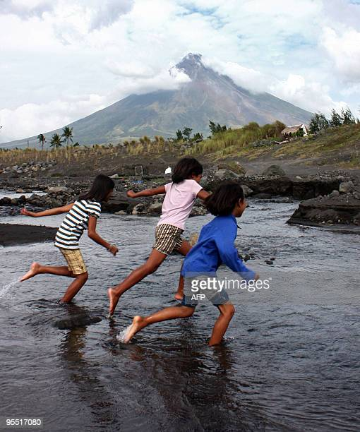 Children play along a river near the famous Cagsawa ruins before a back drop of the Mayon volcano in Legazpi City the Philippines' Albay province on...