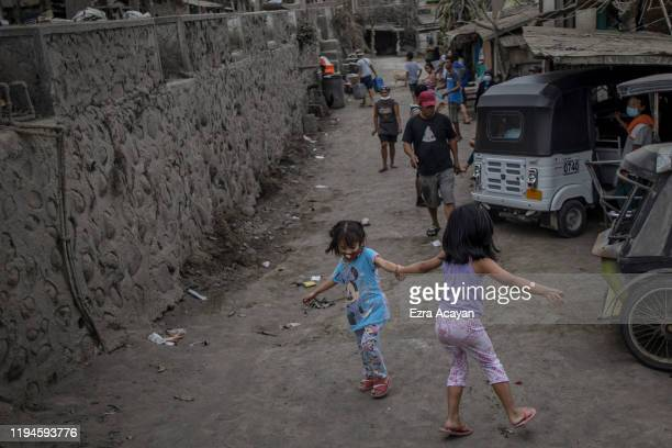 Children play along an ash covered street on January 19 2020 in the outskirts of Tagaytay city Cavite province Philippines The Philippine Institute...