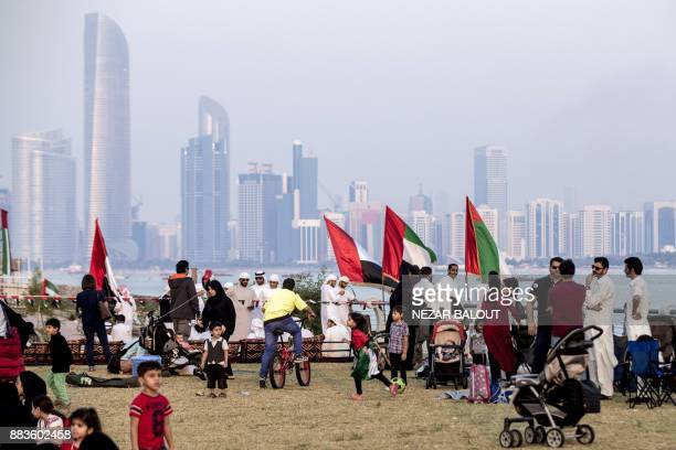 Children play along the corniche as spectators gather to watch UAE's AlFursan National Aerobatic Team performing in the capital Abu Dhabi on December...