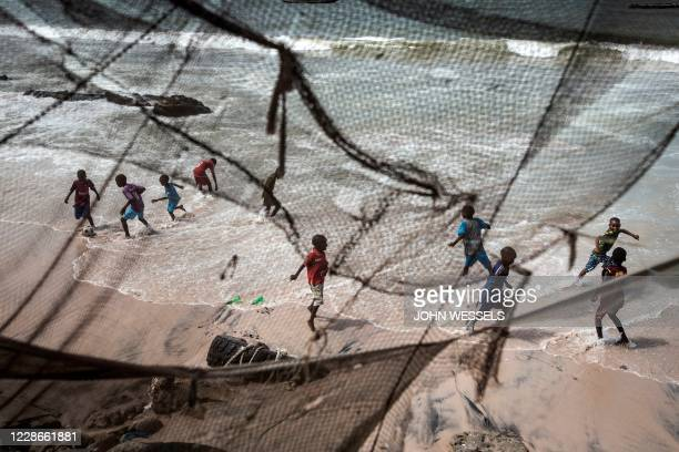 Children play along the eroded coastline after the tide recedes in Bargny on August 18, 2020. - Fishing villages like Bargny have been fighting the...