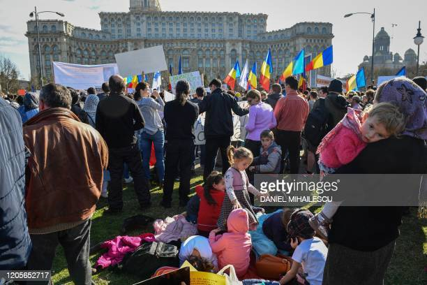 Children play among protesters during a demonstration against a draft law to be adopted by the Romanian Parliament which will make vaccination...