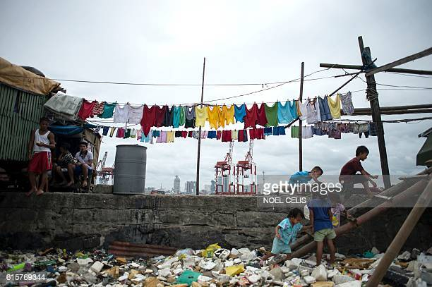 Children play amongst the garbage washed ashore as a result of a storm surge of typhoon Haima close to the breakwater at Baseco Tondo in Manila on...