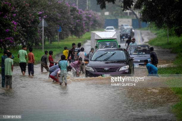 Children play around as motorists pass along a flooded street during monsoon rainfalls in Islamabad on August 25, 2020.