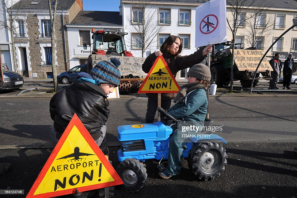 Children play around placards reading 'Airport, No !' as opponents of the Notre-Dame des Landes airport demonstrate on March 20, 2013 outside the Saint-Nazaire courthouse.