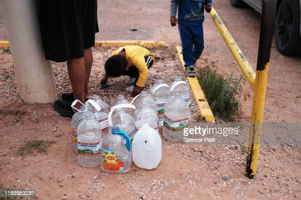 Children play as a woman a member of the Navajo Nation fills bottles of water at a public tap on June 05 2019 in Thoreau New Mexico Due to a legacy...