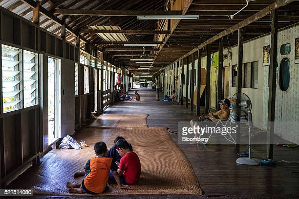 Children play as Iban men sit and talk in the public area of a traditional longhouse in the village of Ensika in Simunjan district Sarawak Malaysia...