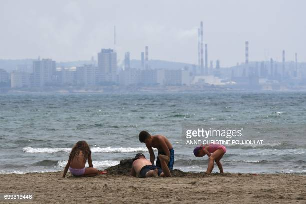 Children play at a beach in FossurMer southern France on June 21 as fumes rise from the chimney of a refinery plant in the background The...