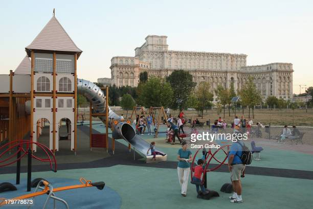Children play at a playground as the Palace of the Parliament built by former Romanian dictator Nicolae Ceausescu looms behind on September 6 2013 in...