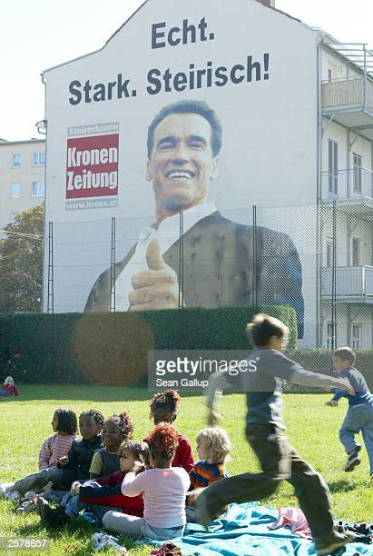 Children play at a school playground under a massive billboard of newly elected California Governor Arnold Schwarzenegger that reads 'Real Strong...