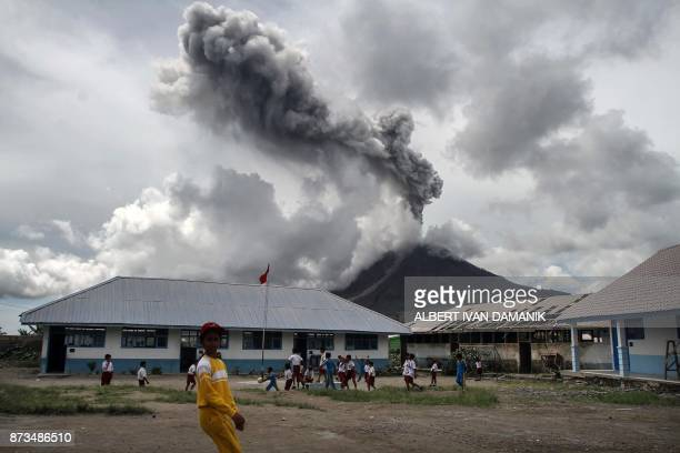 TOPSHOT Children play at an elementary school as the Mount Sinabung volcano spews smoke in Karo on November 13 2017 Sinabung roared back to life in...
