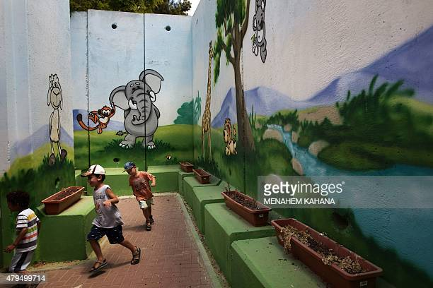 Children play at kindergarten surrounded by decorated concrete blast walls designed to protect from rocket and mortar fire on June 24 in the southern...