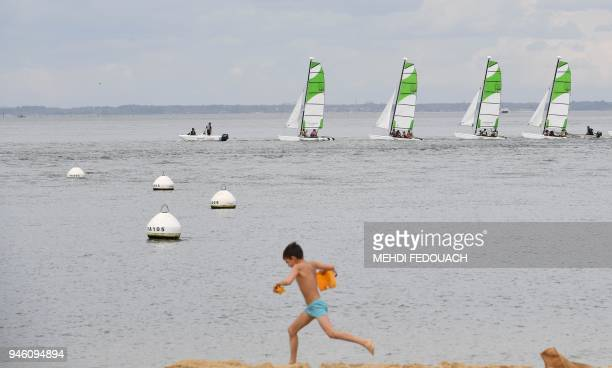 Children play at the beach as tourists sail at the seaside resort town of Arcachon southwestern France on April 13 2018 The tourist town is trying to...