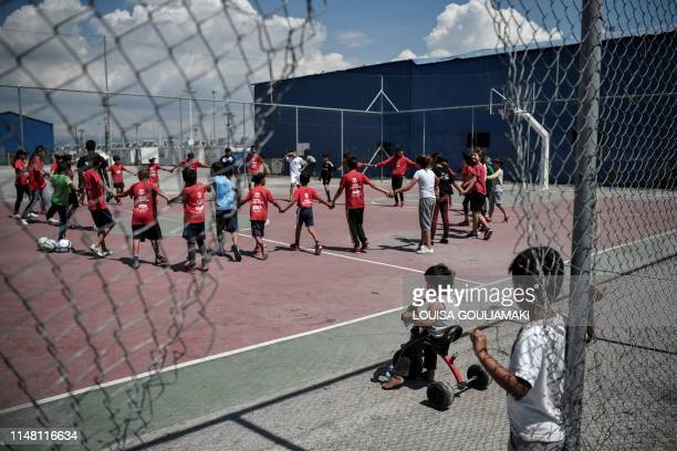 Children play at the Skaramangas refugee camp on the outskirts of Athens on June 5 during an event organised by the Barca foundation which includes...