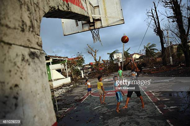 Children play basketball at sunset in Tacloban on November 21 2013 in Leyte Philippines Typhoon Haiyan which ripped through the Philippines over a...