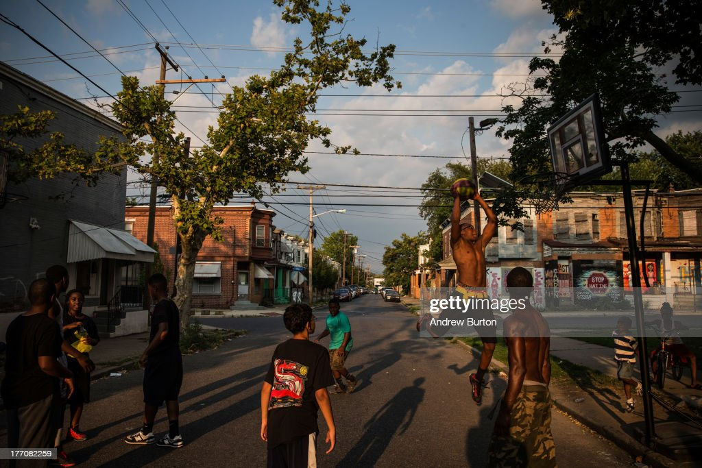 Children play basketball in the street on August 20, 2013 in the Whitman Park neighborhood of Camden, New Jersey. The town of Camden, which was once a large industrial town but watched it's population dwindle as manufacturing left, has been marred with societal problems including high unemployment, crime, murder and heavy drug trafficking for decades. The Camden County Police Department was officially created in May, 2013, after the unionized Camden Police department was disbanded. The overhaul, which was supported by New Jersey Governor Chris Christie, has been considered unprecendented and has been closely watched around the country. The new force currently has approximately 280 members, and will reach full size by December, with 400 members. Early signs suggest the overhaul has been effective - The Wall Street Journal reported earlier this month that Camden murder rates fell 29% from May, 2013 to July 2013, compared to the same period last year. Absentee rates of the CCPD is also lower: approximately 5% of officers have been reported absent so far, compared to approxmiately 30% of the Camden Police Department prior to the change in command.
