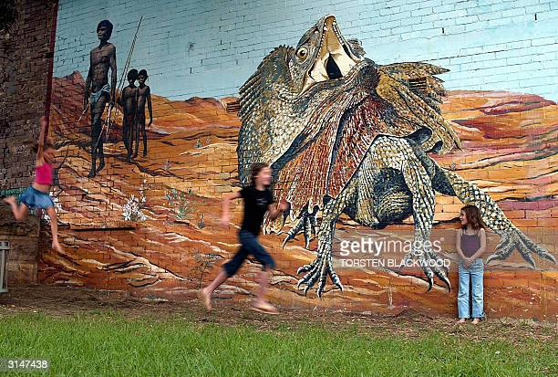 Children play beneath a desert mural featuring a giant frilledneck lizard and Aborigines on walkabout at Reconciliation Park in Sydney 28 March 2004...