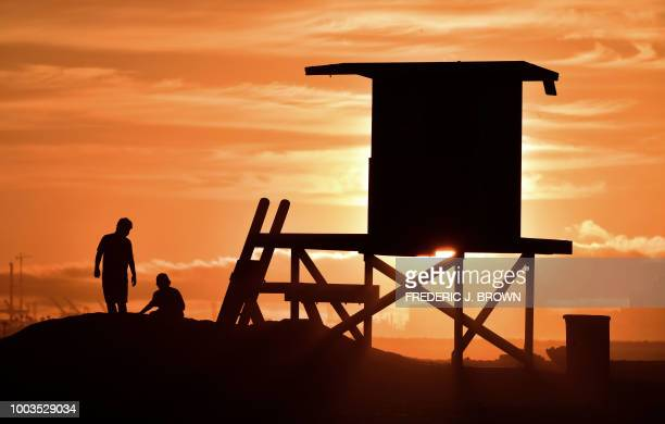 TOPSHOT Children play beside a lifeguard tower as sunset approaches at Sunset Beach in Huntington Beach California on July 21 2018 An Excessive Heat...