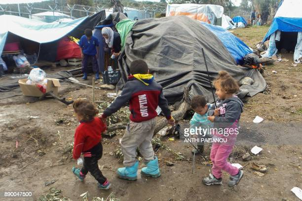 Children play by their families' tents at the overcrowded Moria migrant camp on the island of Lesbos on December 10 2017 On the islands of Lesbos...