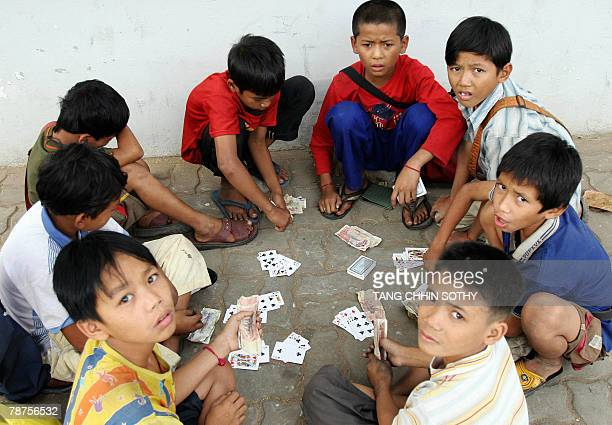 Children play cards at sidewalk along a street in Phnom Penh 03 January 2008 More than half of Cambodian children aged under 14 are being put to work...