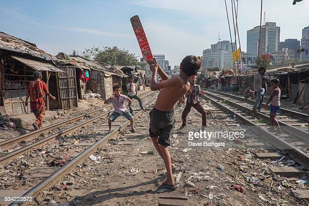 Children play cricket between passing trains at Kaoran Bazar railway slum Dhaka Bangladesh
