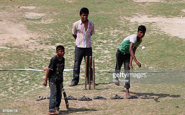 Children play cricket in a field adjacent to the Jahur Ahmed Chowdhury Stadium during day one of the tour match between Bangladesh A and England at...
