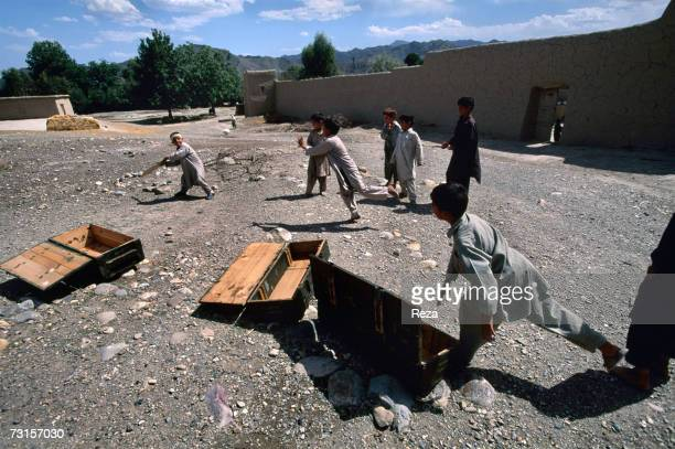 Children play cricket in the middle of empty munitions boxes in the Pashtun tribale zone next to Parachinar in a Shiite village on July 2004 in...