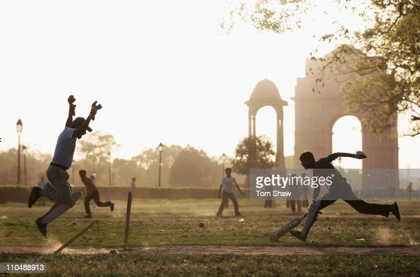 Children play cricket on the park near the India Gate on March 20 2011 in Delhi India