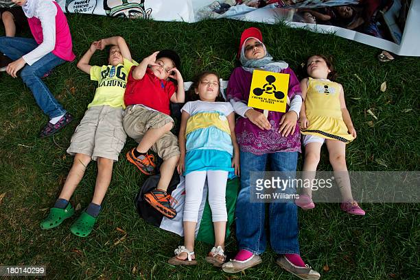 Children play dead as a form of protest to draw attention to the use of chemical weapons in the Syrian civil war during a rally on the east front of...