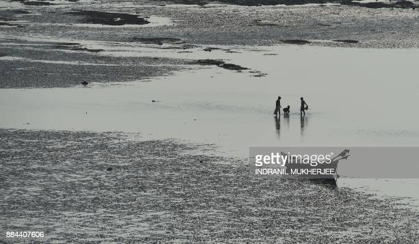 Children play during low tide at the Versova beach in Mumbai on December 2 2017 / AFP PHOTO / INDRANIL MUKHERJEE