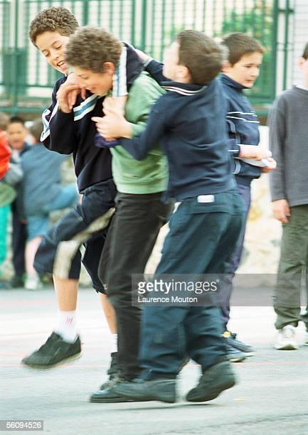 Children play fighting in schoolyard