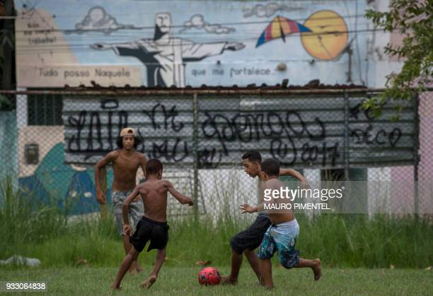 Children play football during a social event organized by the Brazilian Armed Forces at Vila Kennedy favela in Rio de Janeiro Brazil on March 17 2018...