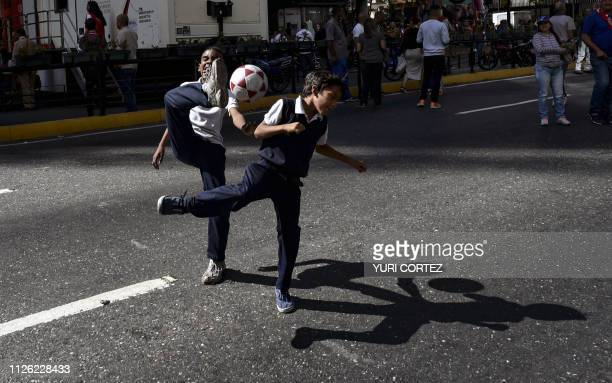 Children play football in a street during an 'antiimperialist day' in support of Venezuelan President Nicolas Maduro in Caracas on February 20 2019...