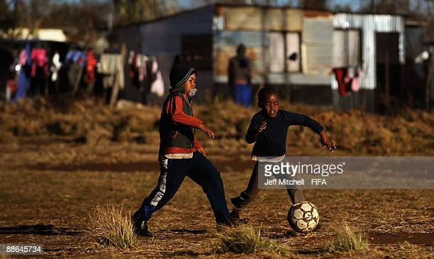 Children play football in Soweto township on June 23, 2009 in Johannesburg, South Africa. South Africa is currently hosting the FIFA Confederations...