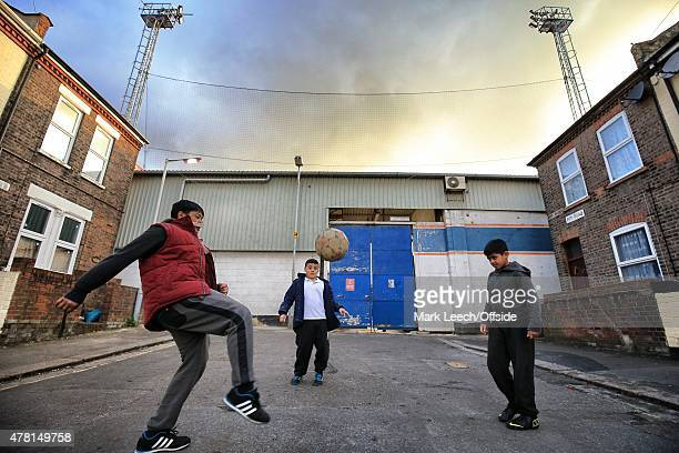 Children play football in the street against the backdrop of floodlights at Kenilworth Road renamed the Prostate Cancer UK stadium for one night only...
