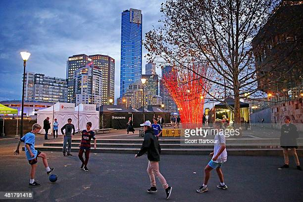 Children play football in the street as they make their way to the MCG to attend the International Champions Cup match between Real Madrid and...